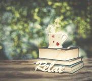 Κούπα και βιβλία φλυτζανιών καφέ πέρα από τον ξύλινο πίνακα υπαίθρια, στο afternoo Στοκ Φωτογραφίες