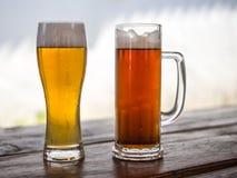 Κούπα και γυαλί μπύρας με τα ελαφριά ή σκοτεινά ποτά Στοκ φωτογραφία με δικαίωμα ελεύθερης χρήσης