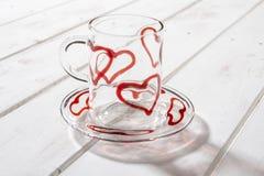 Κούπα και πιατάκι κρυστάλλου με τις κόκκινες καρδιές πέρα από την ξύλινη επιτροπή Στοκ Εικόνες