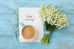 Κούπα καφέ με την ανθοδέσμη του κρίνου λουλουδιών της κοιλάδας και της καλημέρας σημειώσεων στον τυρκουάζ αγροτικό πίνακα άνωθεν