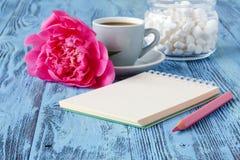 Κούπα καφέ πρωινού, κενό σημειωματάριο, μολύβι και άσπρο peony flowe στοκ εικόνες