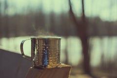 Κούπα μετάλλων που κρατά το καυτό υγρό στα ξύλα Στοκ Εικόνες