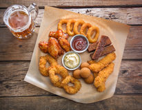 Κούπα με την μπύρα και ένα πρόχειρο φαγητό μπύρας Στοκ φωτογραφία με δικαίωμα ελεύθερης χρήσης