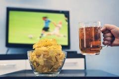Κούπα μπύρας με την μπύρα υπό εξέταση ένα άτομο δίπλα στα τσιπ στο υπόβαθρο μιας μεγάλης TV στην οθόνη που είναι ένας αγώνας ποδο Στοκ εικόνα με δικαίωμα ελεύθερης χρήσης