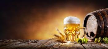 Κούπα μπύρας με το σίτο και λυκίσκοι στο κελάρι στοκ φωτογραφία με δικαίωμα ελεύθερης χρήσης