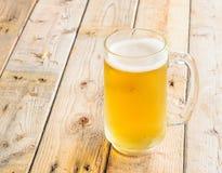 Κούπα μπύρας στο ξύλινο επιτραπέζιο υπόβαθρο Στοκ εικόνα με δικαίωμα ελεύθερης χρήσης