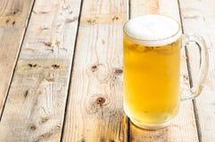 Κούπα μπύρας στο ξύλινο επιτραπέζιο υπόβαθρο Στοκ φωτογραφία με δικαίωμα ελεύθερης χρήσης