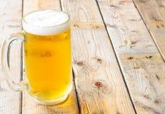 Κούπα μπύρας στο ξύλινο επιτραπέζιο υπόβαθρο Στοκ Φωτογραφία