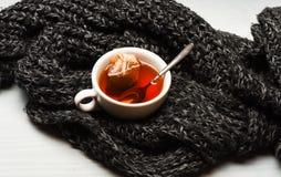 Κούπα που γεμίζουν με το βραστό νερό, teabag και το κουτάλι στο πλεκτό υπόβαθρο μαντίλι Φλυτζάνι τσαγιού και βυθισμένη τσάντα του στοκ φωτογραφίες