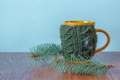 Κούπα στην πλεκτή κάλυψη που στέκεται δίπλα σε Χριστούγεννα Στοκ Φωτογραφία