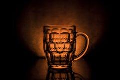 Κούπα της μπύρας σε ένα σκοτεινό υπόβαθρο με το φως Στοκ φωτογραφία με δικαίωμα ελεύθερης χρήσης