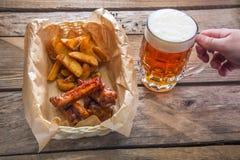 Κούπα της μπύρας υπό εξέταση και ένα πιάτο με ένα πρόχειρο φαγητό μπύρας Στοκ φωτογραφίες με δικαίωμα ελεύθερης χρήσης