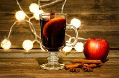 Κούπα του θερμαμένου κρασιού με τα καρυκεύματα κοντά επάνω Apple, ραβδιά κανέλας και γλυκάνισο αστεριών σε έναν ξύλινο πίνακα, φα Στοκ Φωτογραφία