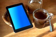 κούπα του καφέ και της ταμπλέτας πρωινού στον πίνακα Στοκ Φωτογραφία