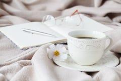 Κούπα του καφέ πρωινού στο κρεβάτι, που διαβάζει ένα βιβλίο, λουλούδι άνοιξη Στοκ Εικόνες
