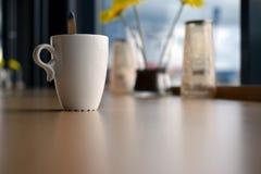 Κούπα του καφέ στον πίνακα στον καφέ Στοκ Εικόνα