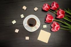 Κούπα του καφέ, του καθαρού χαιρετισμού, marshmallow και των ρόδινων τουλιπών Μαύρη ανασκόπηση Τοπ όψη Στοκ φωτογραφίες με δικαίωμα ελεύθερης χρήσης