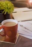 Κούπα του τσαγιού ή του καφέ στην επιφάνεια εργασίας με τα σημειωματάρια και τα έγγραφα και εγκαταστάσεις στοκ εικόνα με δικαίωμα ελεύθερης χρήσης