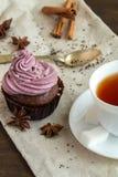 Κούπα του blacktea με τη σοκολάτα cupcakes Στοκ Εικόνες