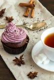 Κούπα του blacktea με τη σοκολάτα cupcakes Στοκ Φωτογραφίες