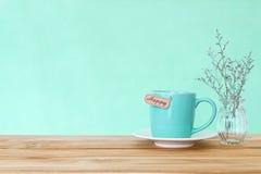 Κούπα φλυτζανιών καφέ με την ευτυχή ετικέττα λέξης στον ξύλινο πίνακα, ειδύλλιο και Στοκ Εικόνα