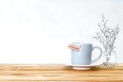 Κούπα φλυτζανιών καφέ με την ευτυχή ετικέττα λέξης στον ξύλινο πίνακα, ειδύλλιο και Στοκ φωτογραφία με δικαίωμα ελεύθερης χρήσης