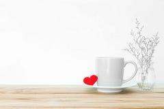 Κούπα φλυτζανιών καφέ με την κόκκινη μορφή καρδιών στον ξύλινο πίνακα, ειδύλλιο Στοκ εικόνα με δικαίωμα ελεύθερης χρήσης