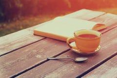 Κούπα φλυτζανιών καφέ πέρα από τον ξύλινο πίνακα υπαίθρια, στο χρόνο απογεύματος Εκλεκτική εστίαση Στοκ εικόνα με δικαίωμα ελεύθερης χρήσης