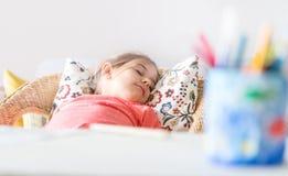 Κούρασε λίγο προσχολικό ύπνο κοριτσιών στην άνετη καρέκλα κοντά στο γραφείο στοκ φωτογραφία με δικαίωμα ελεύθερης χρήσης