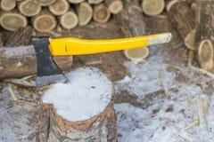 Κούτσουρα τσεκουριών και περικοπών για την ξύλινη πυρκαγιά το χειμώνα στοκ φωτογραφία