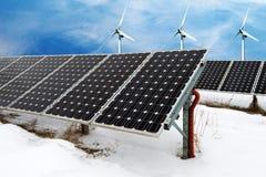 Κολάζ φωτογραφιών των ηλιακών πλαισίων και του αέρα turbins το χειμώνα με το χιόνι Στοκ Εικόνες