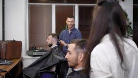 Κολεκτίβα των κομμωτών που εργάζονται από κοινού Αυτοί που δημιουργούν hairstyles Καθημερινή σκηνή από το barbershop φιλμ μικρού μήκους