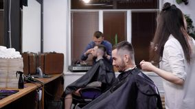 Κολεκτίβα των κουρέων στην εργασία Άποψη της σκηνής της εργασίας στο barbershop Πελάτες που κάθονται στις καρέκλες απόθεμα βίντεο
