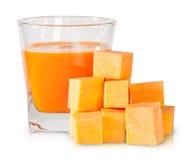 Κολοκύθα που χωρίζονται σε τετράγωνα και ένα ποτήρι του χυμού κολοκύθας Στοκ εικόνα με δικαίωμα ελεύθερης χρήσης