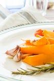 Κολοκύθα που ψήνεται με το σκόρδο και το δεντρολίβανο Στοκ Φωτογραφία