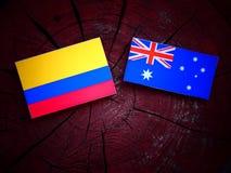 Κολομβιανή σημαία με την αυστραλιανή σημαία σε ένα κολόβωμα δέντρων που απομονώνεται Στοκ Φωτογραφίες