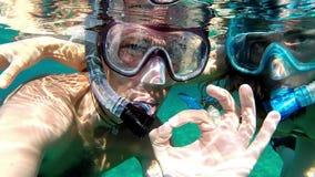 Κολυμπώντας με αναπνευτήρα ζεύγος που κάνει το εντάξει σημάδι - σε αργή κίνηση απόθεμα βίντεο