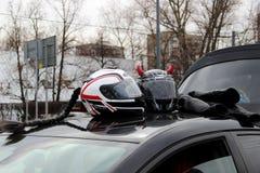 Κράνη μοτοσικλετών με τα ρόδινα κέρατα και μαύρη πλεγμένη τρίχα στη στέγη ενός αυτοκινήτου Προσοχή το άνοιγμα της εποχής μοτοσικλ στοκ εικόνες