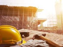 Κράνος ασφάλειας στην επιτραπέζια κορυφή με το εργοτάξιο οικοδομής στο υπόβαθρο στοκ εικόνα με δικαίωμα ελεύθερης χρήσης