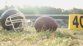 Κράνος και σφαίρα αμερικανικού ποδοσφαίρου που βρίσκονται στην πίσσα, αθλητικές δραστηριότητες καλοκαιρινό εκπαιδευτικό κάμπινγκ απόθεμα βίντεο