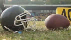 Κράνος και σφαίρα ποδοσφαίρου που βρίσκονται στην πίσσα, φορείς σε ένα σπάσιμο, επαγγελματικά αθλήματα απόθεμα βίντεο