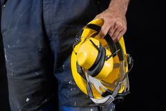 Κράνος που κατέχει ένας εργάτης οικοδομών Προστατευτική ενδυμασία για το μΑ στοκ φωτογραφία