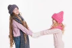 Κράτημα δύο το μικρό αδελφών παραδίδει τα χειμερινά ενδύματα γκρίζο ροζ Οικογένεια Χειμώνας Στοκ Φωτογραφία