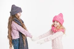 Κράτημα δύο το μικρό αδελφών παραδίδει τα χειμερινά ενδύματα γκρίζο ροζ Οικογένεια Χειμώνας Στοκ φωτογραφία με δικαίωμα ελεύθερης χρήσης