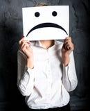 Κράτημα ενός κενού εγγράφου με το λυπημένο πρόσωπο Στοκ Εικόνες