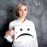 Κράτημα ενός κενού εγγράφου με το λυπημένο πρόσωπο Στοκ Φωτογραφίες