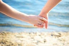 Κράτημα χεριών του νέου ζεύγους ερωτευμένου ενώ απολαμβάνουν Στοκ εικόνα με δικαίωμα ελεύθερης χρήσης