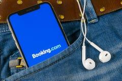 κράτησης εικονίδιο εφαρμογής COM στο iPhone Χ της Apple κινηματογράφηση σε πρώτο πλάνο οθόνης στην τσέπη τζιν Εικονίδιο κράτησης  Στοκ φωτογραφία με δικαίωμα ελεύθερης χρήσης