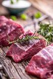 κρέας βόειου κρέατος ακ&al Ακατέργαστη tenderloin βόειου κρέατος μπριζόλα σε έναν πίνακα κοπής με το άλας πιπεριών δεντρολιβάνου  Στοκ Φωτογραφία