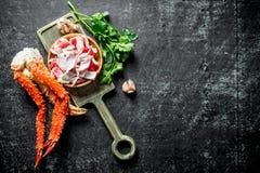 Κρέας καβουριών και φρέσκο καβούρι σε έναν πίνακα κοπής με τα πράσινα και το σκόρδο στοκ εικόνες